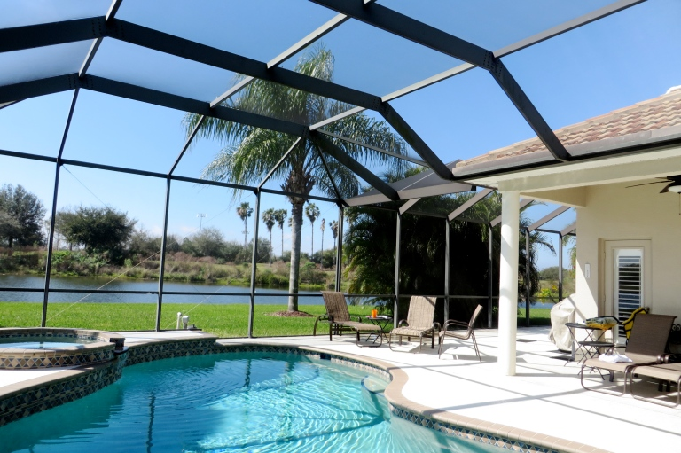 Gorgeous backyard overlooking the pool and lake as you enter the house