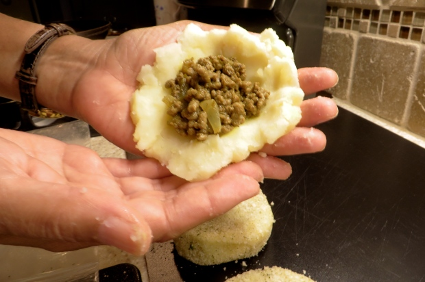 Mash the potato and create a small indentation, add the meat, then cover the top very carefully.